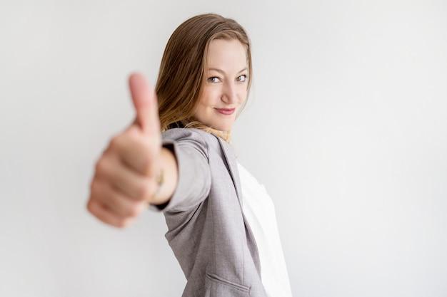 Mulher de negócios bonita confiante aparecendo polegar