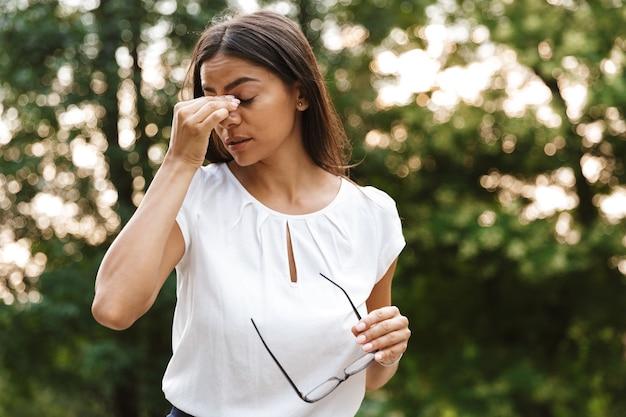 Mulher de negócios bonita e cansada caminhando no parque ao ar livre segurando óculos