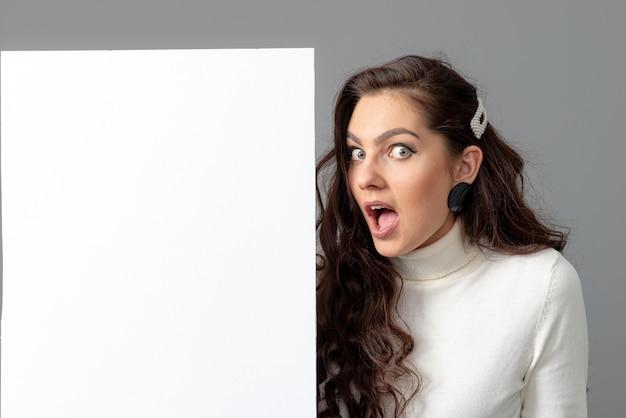 Mulher de negócios bonita e sensual com cabelo longo cacheado mostra um quadro de avisos em branco, isolado em cinza, copie o espaço