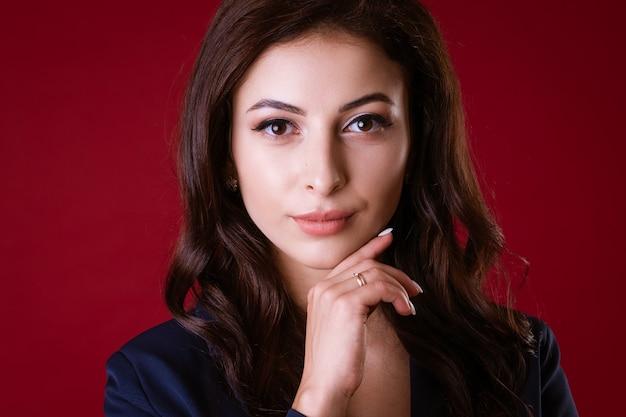 Mulher de negócios bonita em um terno posando na parede vermelha
