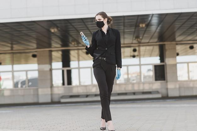 Mulher de negócios bonita em um terno preto em uma máscara médica preta e luvas na cidade em quarentena e isolamento. pandemia covid-19. foco seletivo