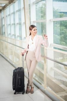 Mulher de negócios bonita está andando no aeroporto, conceito de viagens de negócios