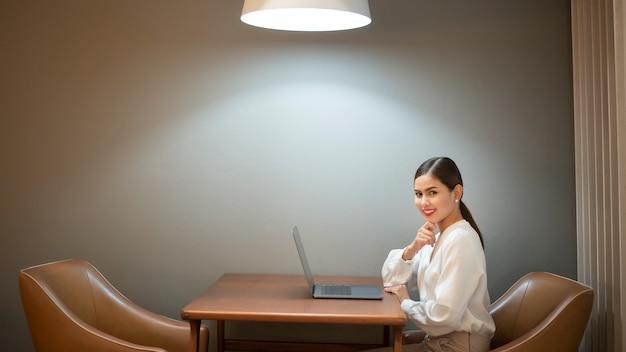 Mulher de negócios bonita está trabalhando com o laptop no café