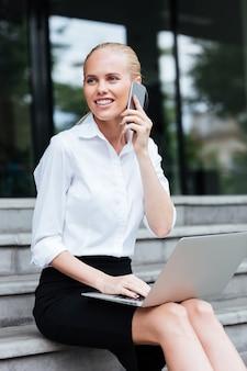Mulher de negócios bonita falando no celular, sentada na escada com o laptop