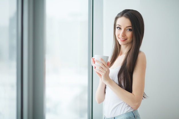 Mulher de negócios bonita jovem com café no escritório moderno brilhante dentro de casa