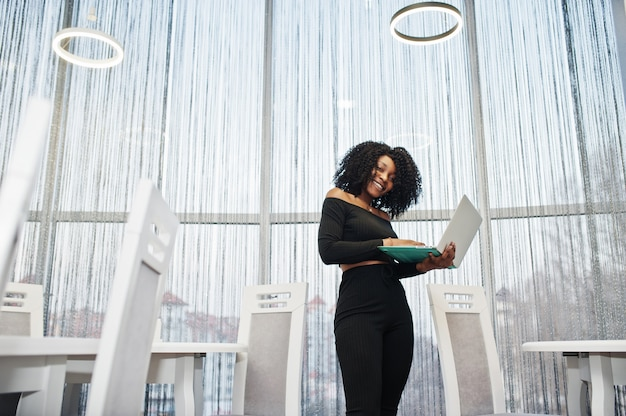 Mulher de negócios bonita jovem elegante com penteado afro usando laptop
