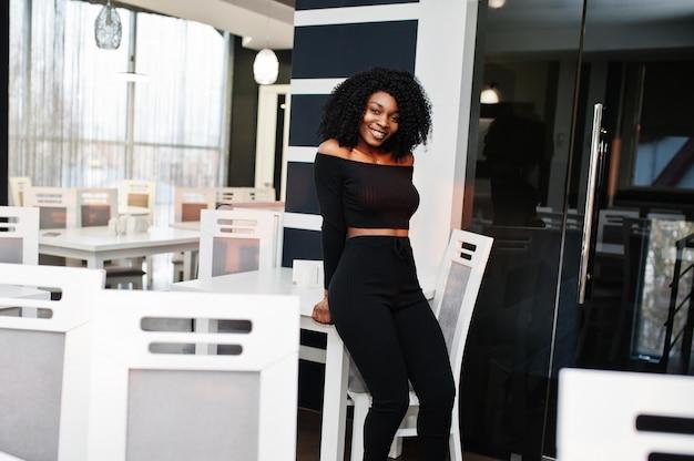 Mulher de negócios bonita jovem elegante com penteado afro, vestindo preto elegante, fique no escritório perto da mesa