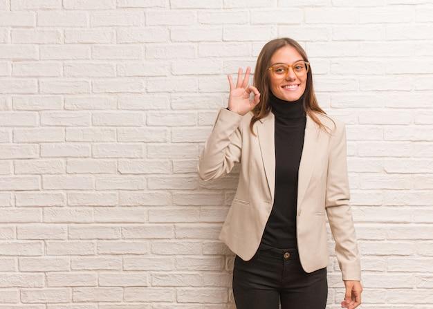 Mulher de negócios bonita jovem empreendedor alegre e confiante, fazendo o gesto de ok