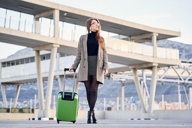 Mulher de negócios bonita jovem no aeroporto internacional com mala