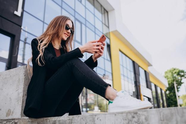 Mulher de negócios bonita jovem pelo centro do escritório, usando o telefone