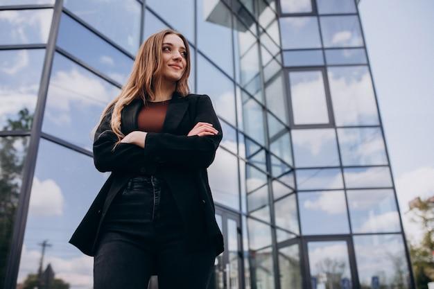 Mulher de negócios bonita jovem pelo centro do escritório