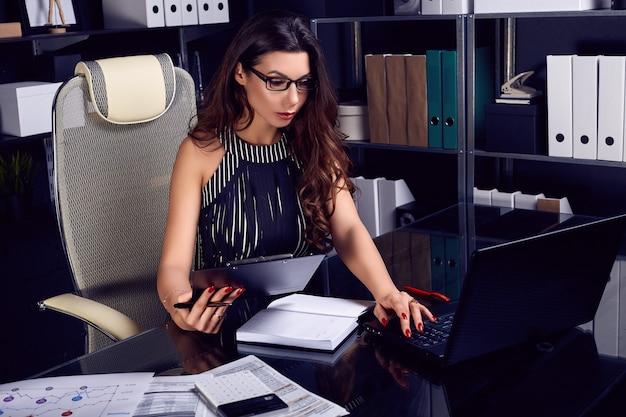 Mulher de negócios bonita jovem trabalhando na mesa preta elegante