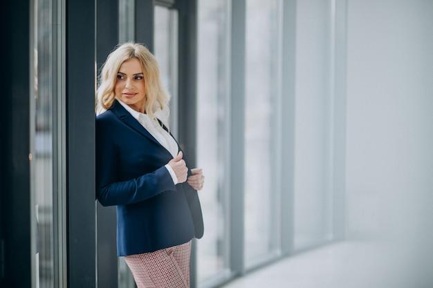 Mulher de negócios bonita no escritório perto da janela