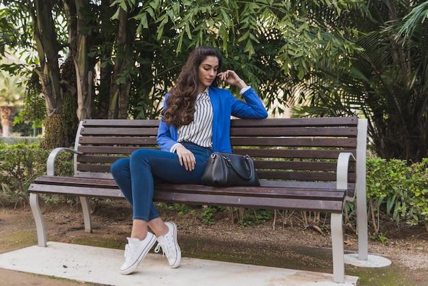 Mulher de negócios bonita que pensa no parque