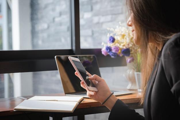 Mulher de negócios bonita que usa o dispositivo do smartphone nas mãos.