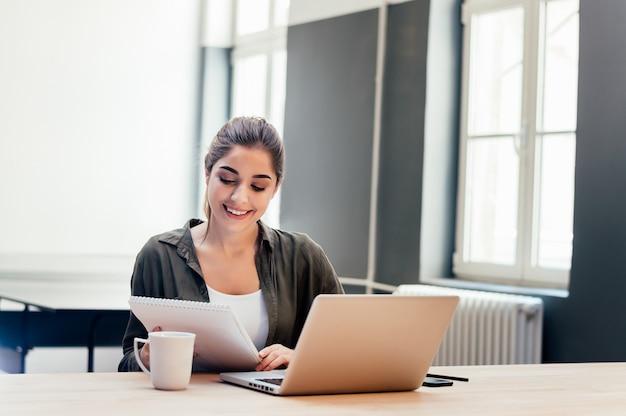 Mulher de negócios bonita que verifica o original e que usa o caderno e o sorriso.