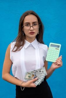 Mulher de negócios bonita segurando calculadora na parede azul