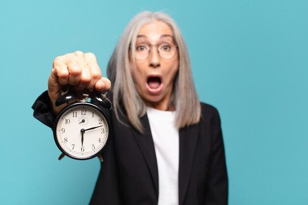 Mulher de negócios bonita sênior com um despertador. conceito de tempo