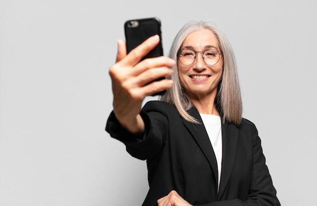 Mulher de negócios bonita sênior com um smartphone.