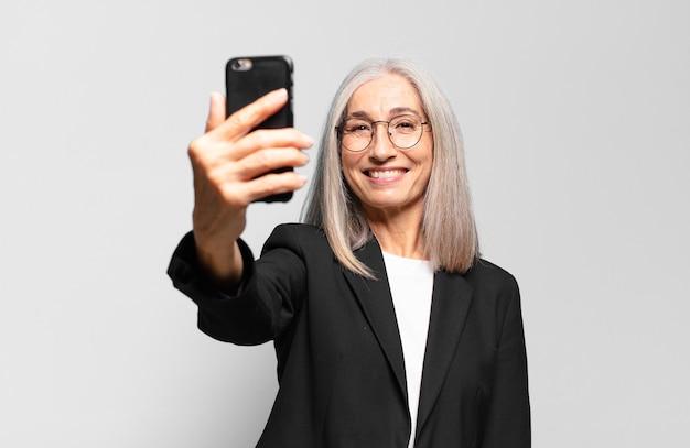 Mulher de negócios bonita sênior com um telefone inteligente.