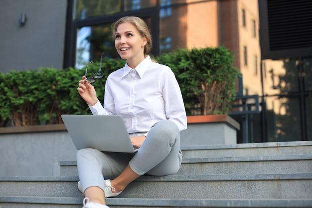 Mulher de negócios bonita sentada perto do centro de negócios e usando o laptop.