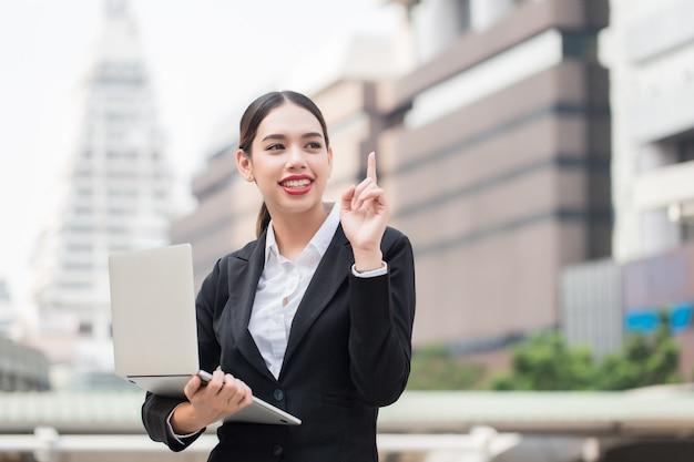Mulher de negócios bonita sorridente moderna usando telefone inteligente e laptop com espaço de cópia