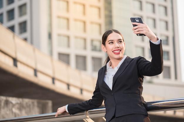 Mulher de negócios bonita sorridente moderna usando telefone inteligente