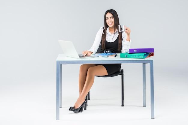 Mulher de negócios bonita sorrindo sentado na mesa trabalhando usando laptop olhando para a tela digitando no laptop isolado no branco