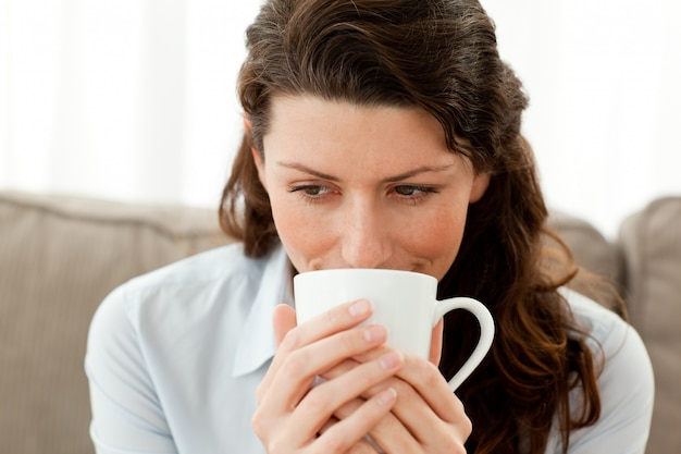 Mulher de negócios bonita tomando café no sofá