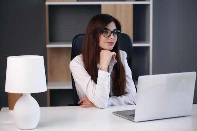 Mulher de negócios bonita usa um laptop e sorri enquanto trabalha no escritório.