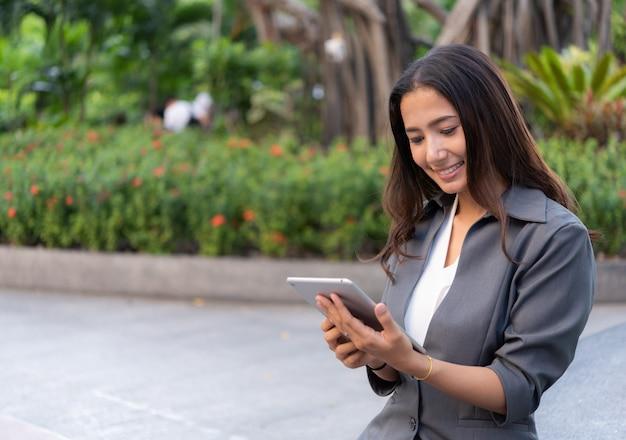 Mulher de negócios bonita usando o ipad para trabalho ao ar livre