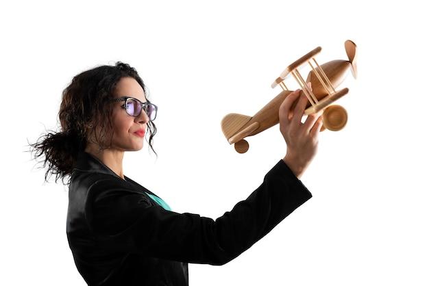 Mulher de negócios brinca com um conceito de aeronave de brinquedo de inicialização de empresa e sucesso comercial isolado na superfície branca