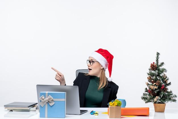 Mulher de negócios brincando com seu chapéu de papai noel, sentada à mesa com uma árvore de natal e um presente