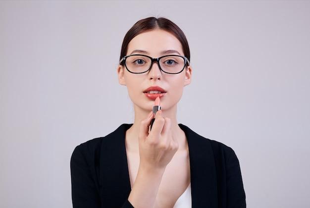 Mulher de negócios calma de aparência agradável com batom rosa na mão direita está de pé sobre um dorso cinza em uma jaqueta preta, camiseta branca e óculos de computador. trabalhador ocupado. copie o espaço.