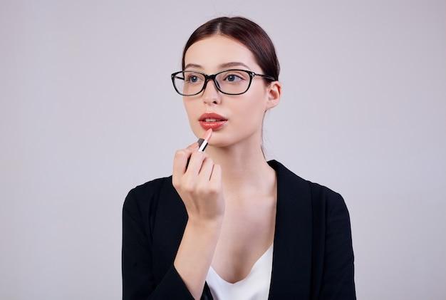 Mulher de negócios calma de aparência agradável com batom rosa na mão direita está de pé sobre um dorso cinza em uma jaqueta preta, camiseta branca e óculos de computador. trabalhando muito. trabalhador ocupado.