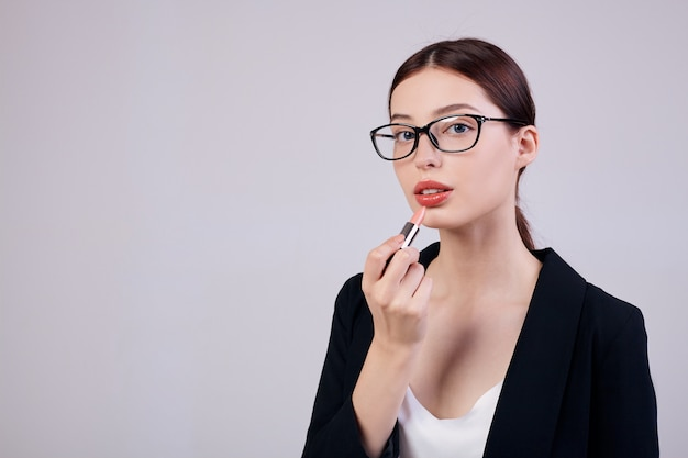 Mulher de negócios calmo de aparência agradável com batom rosa está de pé nas costas cinza em uma jaqueta preta, camiseta branca e óculos de computador. trabalhando muito. trabalhador ocupado.