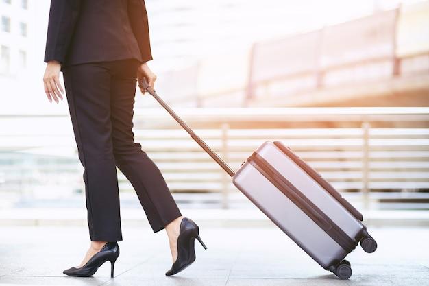 Mulher de negócios, caminhando do lado de fora do prédio de transportes públicos com a bagagem na hora do rush.