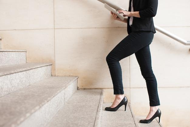 Mulher de negócios caminhando no andar de cima e usando touchpad