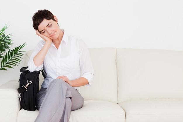 Mulher de negócios cansada com um papel e uma bolsa