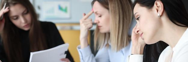 Mulher de negócios cansada e pensativa com documentos e laptops em sua mesa de trabalho. conceito de metas e tarefas de negócios desafiadoras