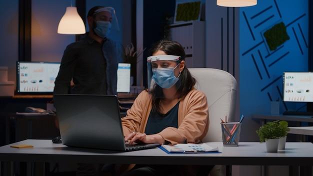 Mulher de negócios cansada e viciada em trabalho com máscara e viseira contra cobiça