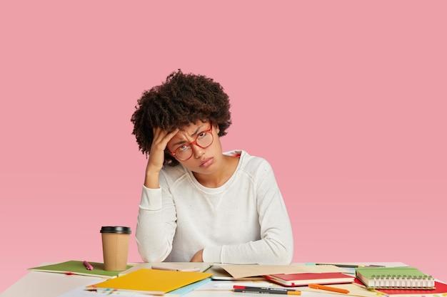 Mulher de negócios cansada, morena, estressada, sente dor de cabeça, parece cansada, mantém a mão na cabeça, usa um suéter branco casual
