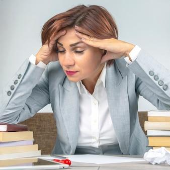 Mulher de negócios cansada no escritório e preocupada com as emoções. estresse e dor de cabeça