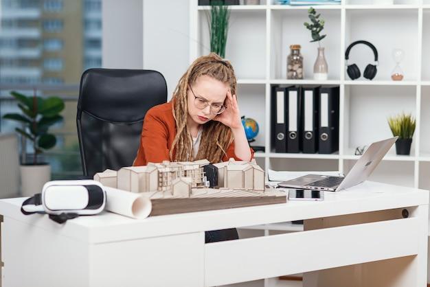 Mulher de negócios cansada, sentindo estresse após novos problemas de projeto arquitetônico e design. conceito sobrecarregado.