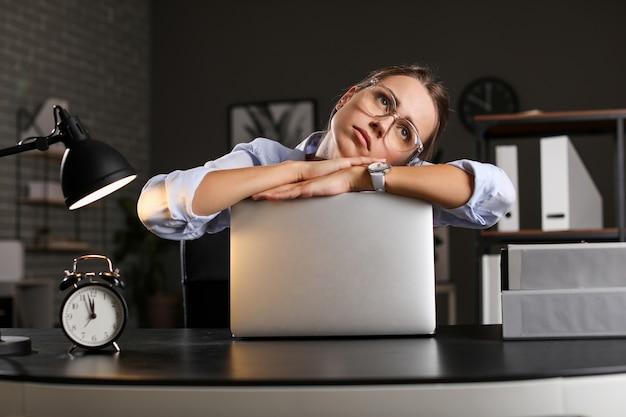 Mulher de negócios cansada tentando cumprir prazo no escritório