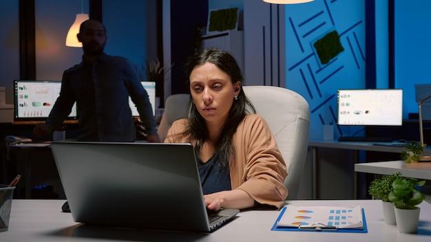 Mulher de negócios cansada, viciada em trabalho, digitando estatísticas financeiras no laptop