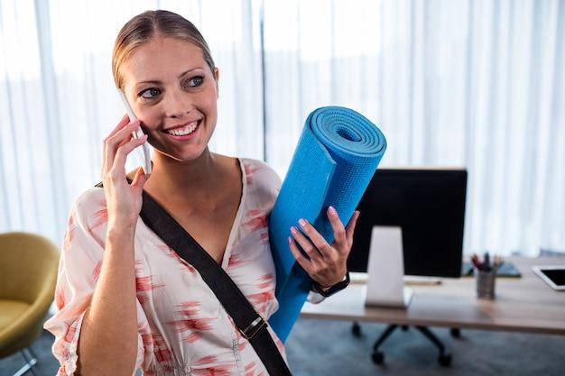 Mulher de negócios casuais segurando o tapete de ioga