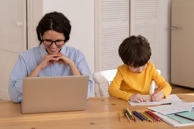 Mulher de negócios casual concentrada lendo e-mail comercial em um laptop próximo ao filho pequeno