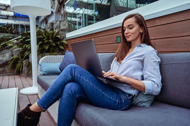 Mulher de negócios casual moderna e inteligente trabalhando remotamente on-line em um laptop