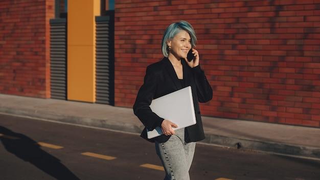 Mulher de negócios caucasiana alegre com cabelo azul andando do lado de fora com um laptop e discutindo no telefone